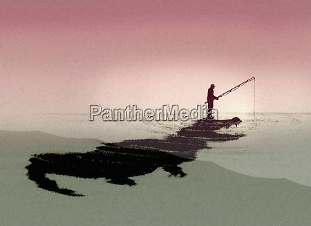 man fishing oblivious of crocodile below
