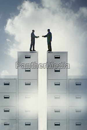 two businessmen reaching to shake hands