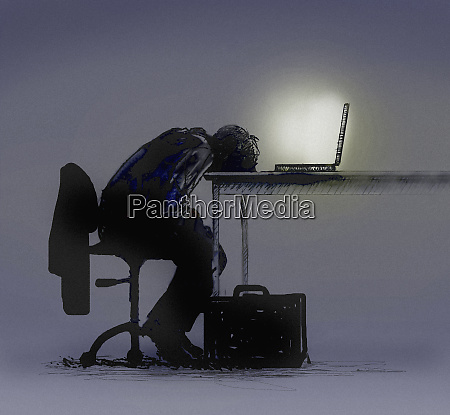 exhausted businessman slumped over laptop computer