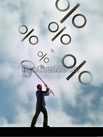 businessman chasing percentage signs with butterfly