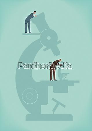 geschaeftsmann mit grossem mikroskop bewacher mit