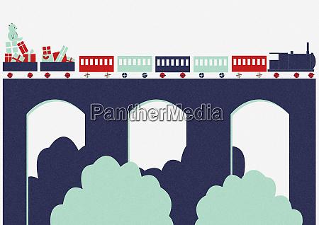 spielzeugzug mit weihnachtsgeschenken auf viadukt