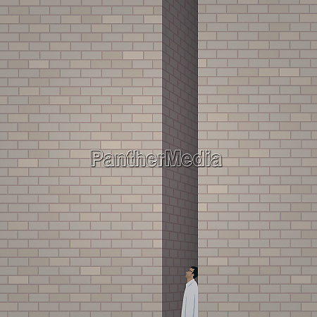 man trapped between two tall brick