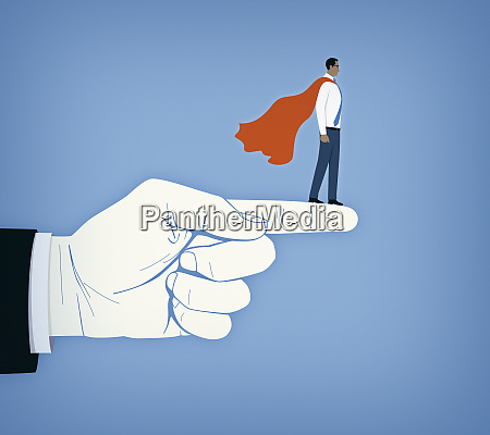 businessman as superhero supported on large