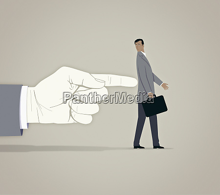 large finger pushing anxious businessman in