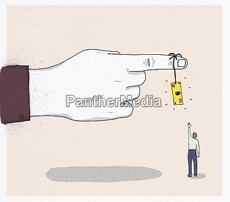 man reaching for dollar bill hanging