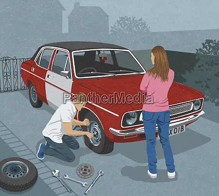 woman watching man repairing flat tire