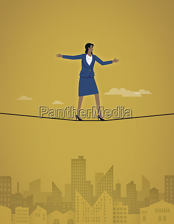 businesswoman balancing on tightrope in high