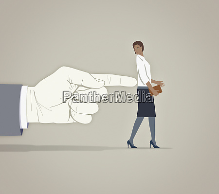 large finger pushing anxious businesswoman in