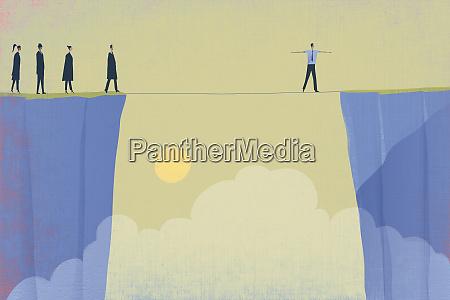 businesspeople watching coworker walking tightrope bridging