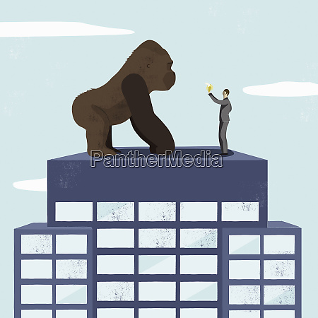 businessman offering banana to large gorilla