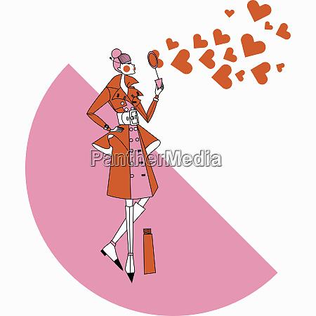 fashionable woman blowing heart shape bubbles