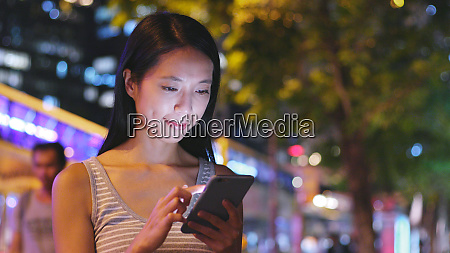 woman sending sms on cellphone at