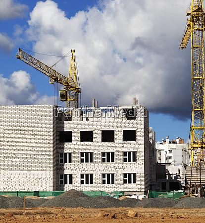 construction cranes and brick building