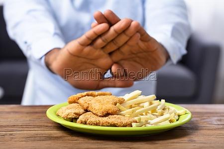 man refusing friend food on plate