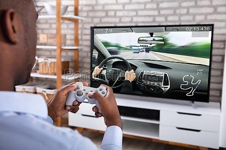 african man playing racing game on