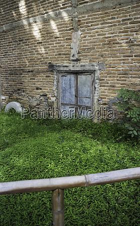zinktor mit alter ziegelmauer und grasfeld