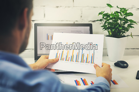 man working with business statistics data