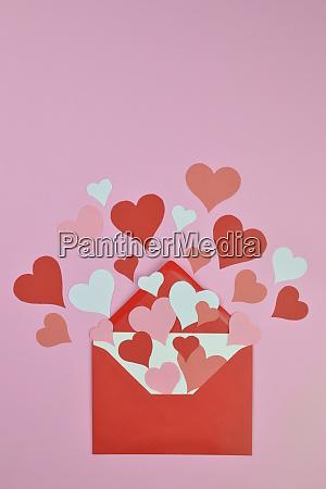 rote und rosa papierherzen in einem