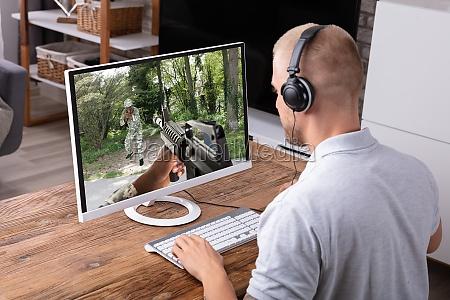 mann spielt actionspiel am computer