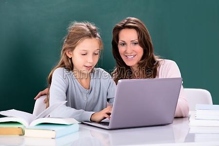 teacher teaching girl on laptop