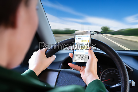 frau prueft textnachrichten auf smartphone fahrendes