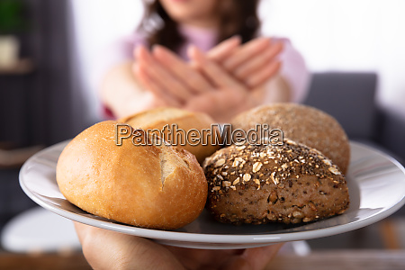 woman refusing bread offered by person