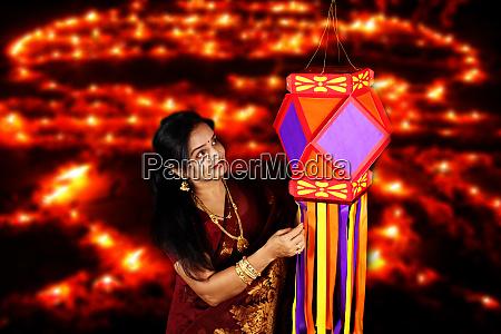 indian woman admiring her diwali lantern