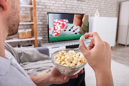 man eating popcorn while watching television
