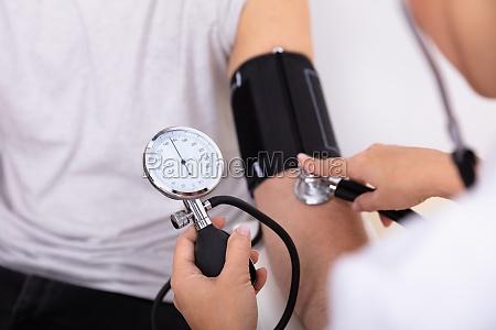 arzt misst blutdruck des patienten