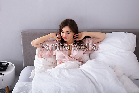 woman stretching her arms on bed