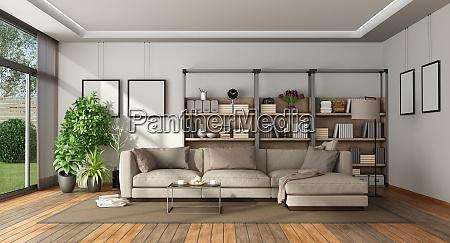 modernes wohnzimmer mit buecherregal und sofa