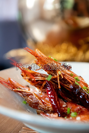 three prawns on white plate cooked