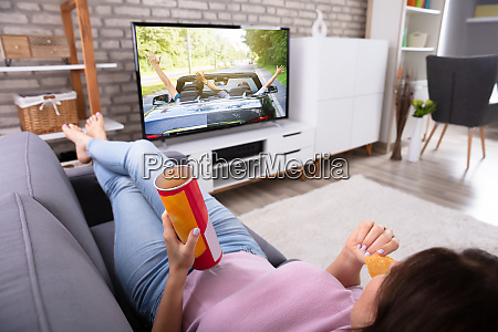 woman eating potato chips while watching