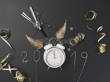 neujahrshintergrund mit weissem wecker auf kreidebrett