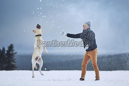 mann spielt mit hund in winterlandschaft