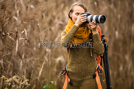 pretty female photographer taking pictures outdoor