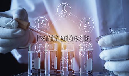 forscher mit chemischen reagenzglaesern im glaslabor