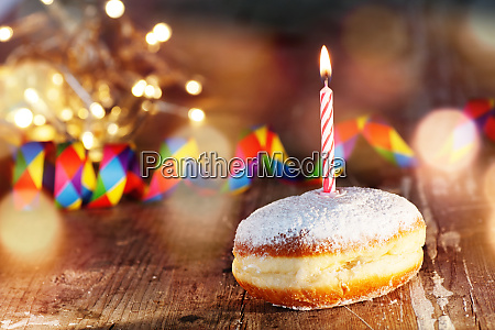 donut with candle and colorful streamers