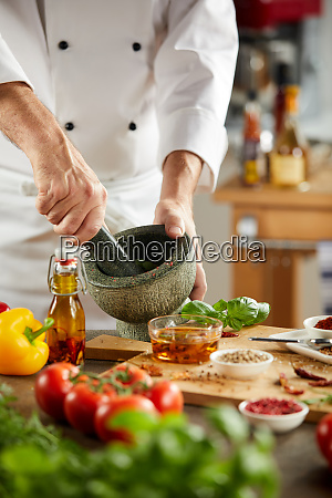 chef grinding fresh herbs in a