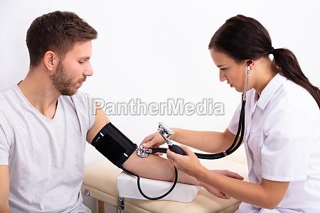 arzt prueft blutdruck des patienten