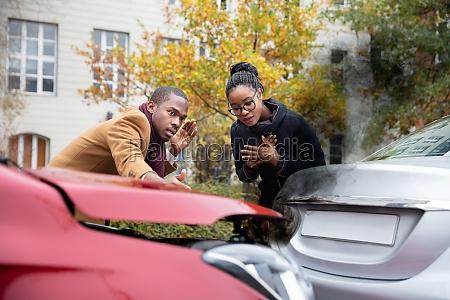 man and woman looking at car