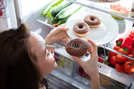 happy woman taking donut from plate