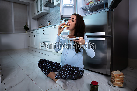 hungry woman eating food in kitchen