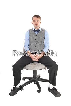 man sitting in dress pants and