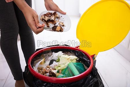 frau werfen kuchen in papierkorb