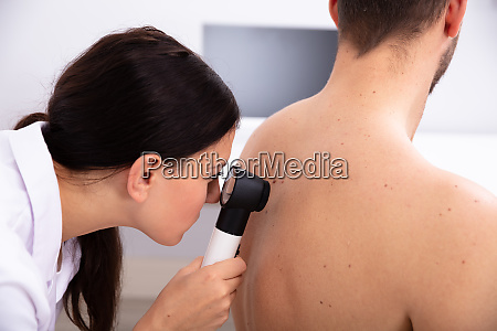 doctor examining pigmented skin on mans