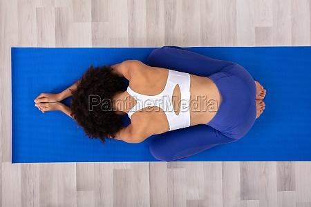 frau macht yoga auf fitness mat
