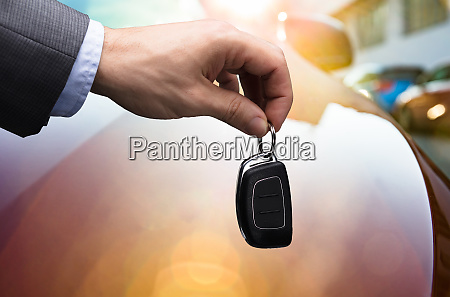 businessperson giving car key to robot