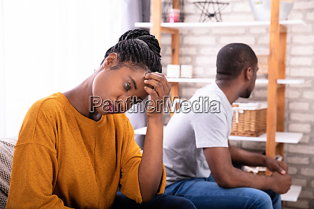 upset african couple sitting on sofa